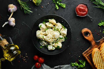 Russian pelmeni meat Dumplings with greens in a black plate. Russian traditional cuisine. Top view. Free copy space.
