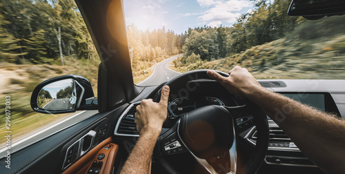 fototapeta na ścianę hands of car driver on steering wheel, Driving car at autumn day on a country road, having fun driving the empty highway on tour journey - POV, first person view shot