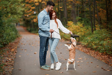 Ginger Beautiful Woman Taming Her Pet, Hugging Her Boyfriend, Dog Standing On Two Legs Full Length Photo