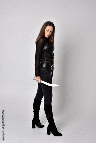 Carta da parati full length portrait of a pretty brunette woman wearing black leather fantasy costume