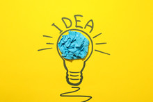 Drawn Light Bulb And Paper Ball On Yellow Background. Good Idea Concept