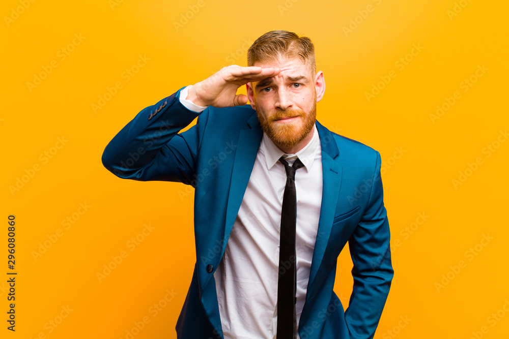 Fototapeta young red head businessman looking bewildered and astonished, with hand over forehead looking far away, watching or searching against orange background