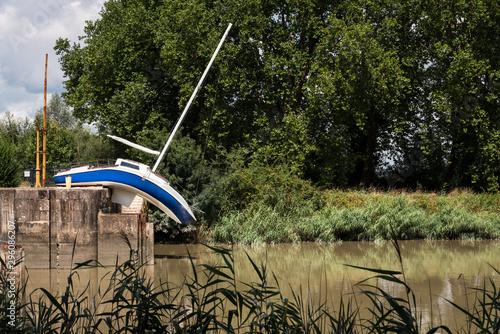 un bateau mou tordu et déformé au bord de l'eau Fototapet