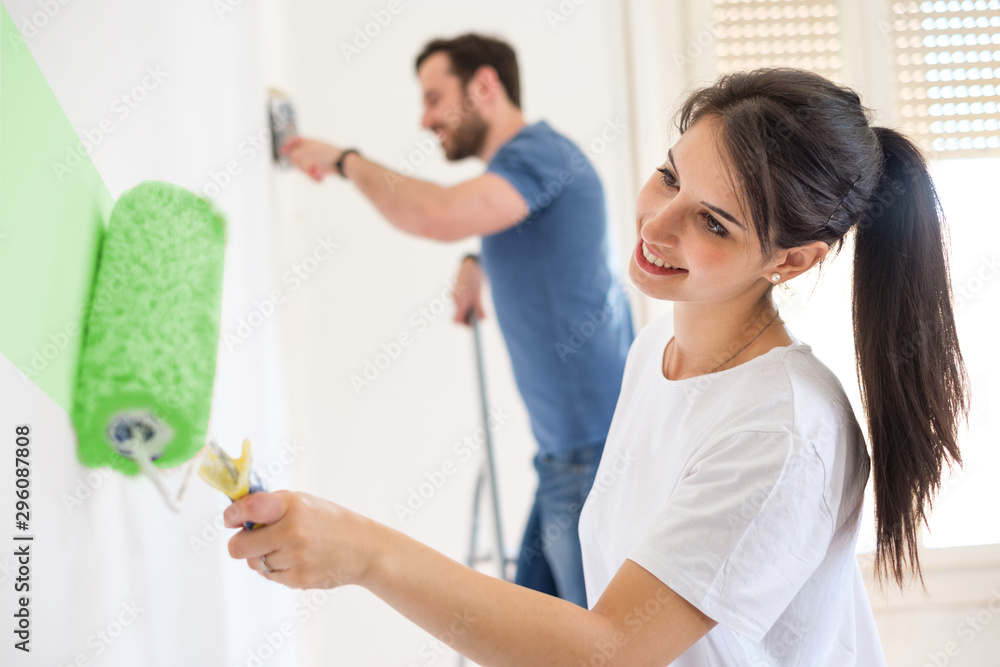 Fototapety, obrazy: Smiling loving couple doing home renovations together