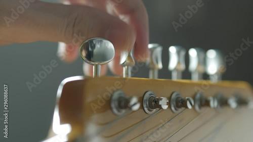 Fotografia, Obraz  Tuning guitar string by adjusting tuning machines