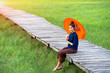 Leinwanddruck Bild - Asian girls wear traditional clothing Hold the red umbrella at countryside,Beautiful Asian women,Thai women are smiling.