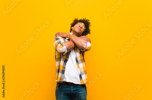 Fotomural  young black man feeling in love, smiling, cuddling and hugging self, staying sin