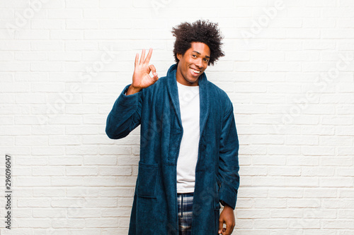 Obraz na plátně  young black man wearing pajamas with gown feeling happy, relaxed and satisfied,