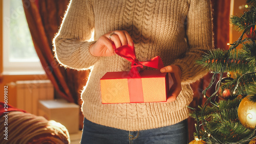 Toned image of young woman unwrapping and opening Christmas gift box Canvas-taulu