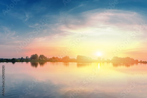 Summer landscape with a lake and sunset above it.