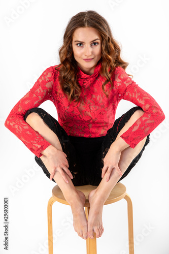 Young woman in black leggings and red long-sleeved blouse sits astride a bar stool Canvas Print