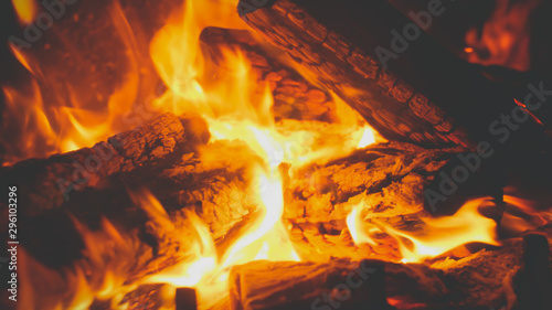 Foto op Plexiglas Brandhout textuur Closeup toned image of fire flames covering burning wooden logs in the fireplace at house