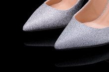 A Pair Of Female Shoes On A Black Background. Shiny Silver Shoes With A Pointed Toe Close-up.