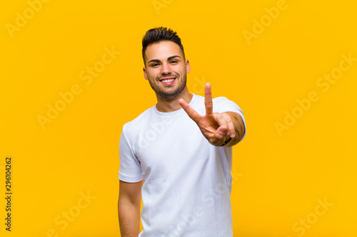 Valokuva  young hispanic man smiling and looking happy, carefree and positive, gesturing v