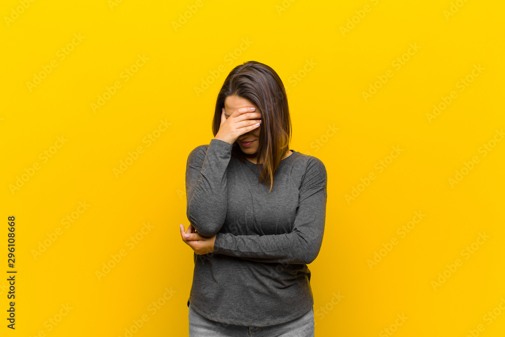 Fototapety, obrazy: latin american woman looking stressed, ashamed or upset, with a headache, covering face with hand isolated against yellow wall