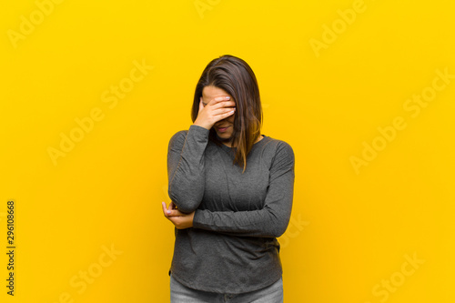 Fotomural  latin american woman looking stressed, ashamed or upset, with a headache, coveri