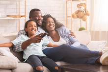 Happy Black Family Relaxing And Watching Tv At Home