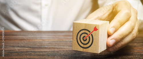 A businessman holds in his hands a wooden block with a target symbol Wallpaper Mural