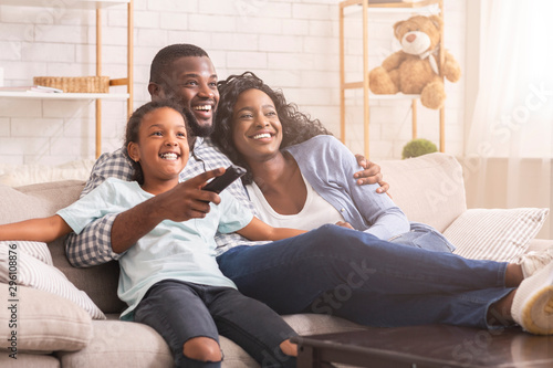 Fotografiet Happy black family relaxing and watching tv at home