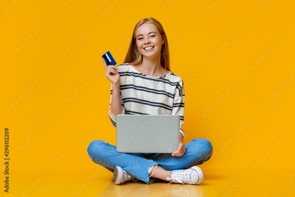 Fototapeta Cheerful girl holding credit card and laptop, sitting on floor