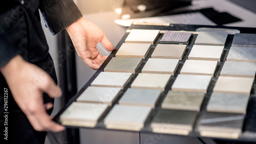 Fotografía Male architect or interior designer hand choosing ceramic texture sample from swatch board in design studio