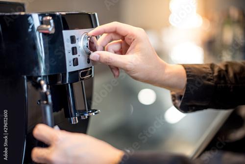 Canvastavla Male barista hand turning button on coffee machine in the kitchen