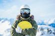 Portrait of man in helmet with snowboard standing on snow resort .