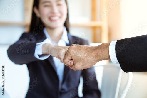 Fotografía  Smiling Asian young businesswoman bump fists with her boss after work success together at an office