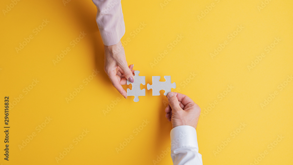Fototapeta Male and female hands joining two matching puzzle pieces together