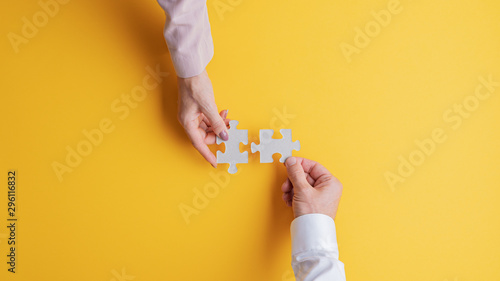 Obraz Male and female hands joining two matching puzzle pieces together - fototapety do salonu