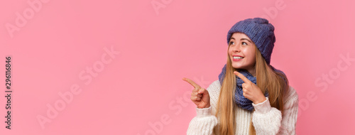 Happy girl pointing at copy space over pink background - 296116846