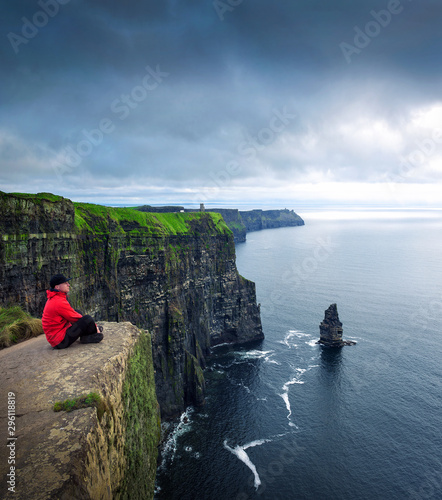 Canvas Print Hiker sitting at the cliffs of Moher