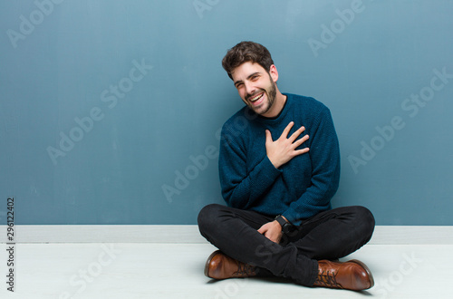 Fotografie, Obraz  young handsome man sitting on floor laughing out loud at some hilarious joke, fe