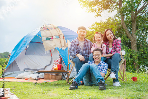 Fotomural  Happy asian family sitting together in front of tent at campping site