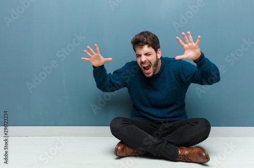 young handsome man sitting on floor screaming in panic or anger, shocked, terrif Wallpaper Mural