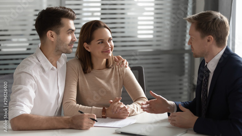 Confident manager consulting young couple about contract at meeting