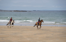 Tourists On Horseback On A Beach In The Ring Of Kerry Peninsula In The Republic Of Ireland