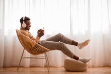 Afro Guy In Headphones Using Smartphone Sitting On Chair Indoor