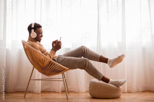 Spoed Foto op Canvas Ontspanning Afro Guy In Headphones Using Smartphone Sitting On Chair Indoor