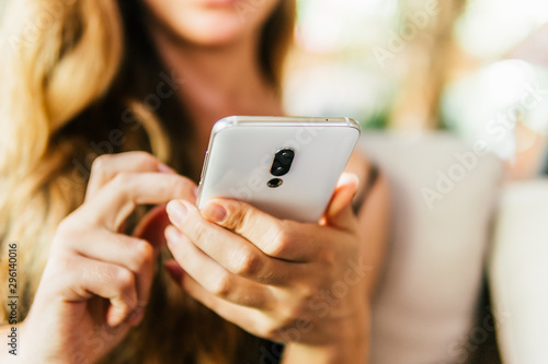 Fototapety, obrazy: Closeup image of a woman hands holding , using smart phone in vintage cafe