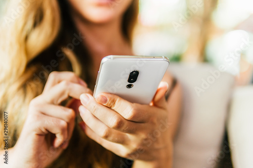 Fototapety, obrazy: side view of young woman using smartphone at table in coffee shop