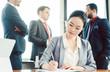 Leinwandbild Motiv Asian business woman doing work while men in background are chatting
