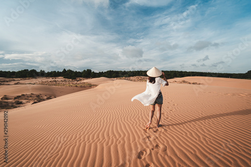 Foto auf AluDibond Rosa dunkel Young woman traveler walking at red sand dunes in Vietnam, Travel lifestyle concept