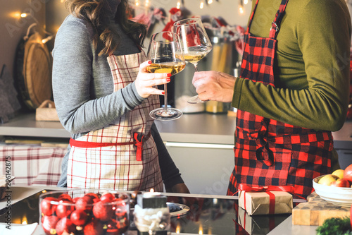 Couple celebrating Christmas in the kitchen and drink wine Tablou Canvas