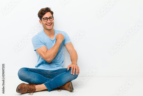 young handsome man feeling happy, positive and successful, motivated when facing Wallpaper Mural