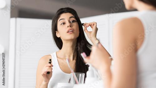 Photo Girl Applying Mascara Looking In Mirror In Bathroom, Panorama
