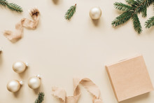 Christmas / New Year Holiday Composition. Mock Up Frame With Blank Copy Space, Fir Needle Branches, Gift Box, Ribbons And Christmas Baubles On Beige Background. Flat Lay, Top View Festive Concept.
