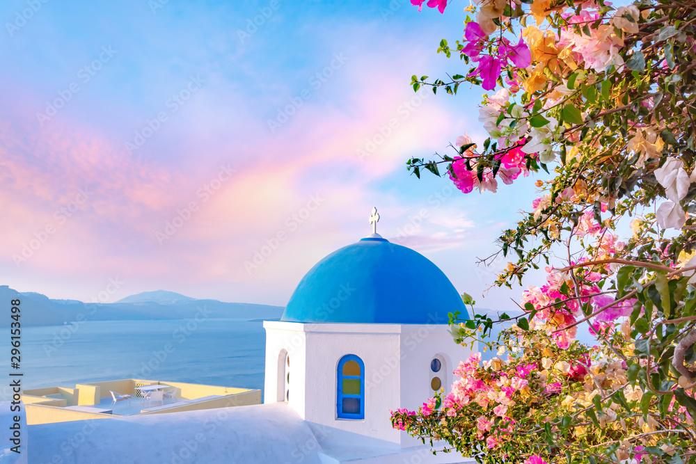 Fototapeta Beautiful Oia town on Santorini island, Greece. Traditional white architecture  and greek orthodox churches with blue domes over the Caldera, Aegean sea.