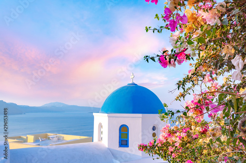 Fototapeta Beautiful Oia town on Santorini island, Greece. Traditional white architecture  and greek orthodox churches with blue domes over the Caldera, Aegean sea. obraz