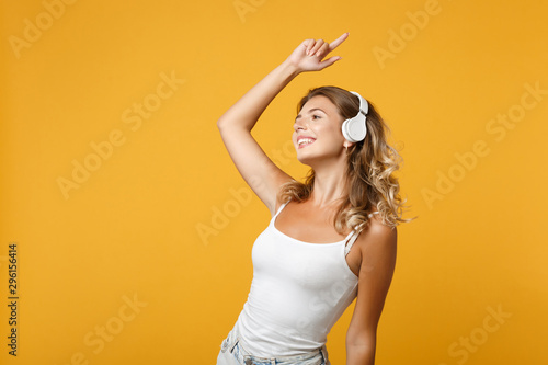 Fototapeten Tanzschule Stunning young woman girl in light casual clothes with headphones posing isolated on yellow orange background, studio portrait. People lifestyle concept. Mock up copy space. Listening music, dancing.